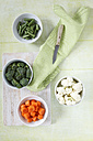 Bowls of broccoli and cauliflower florets, sliced green beans and carrots, kitchen knife and cloth on wood - EVGF000709