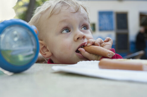 Baby boy eating a sausage - MUF001516