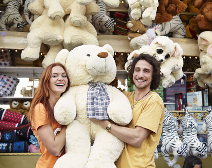Happy young couple on a funfair with large teddy bear - RHF000359