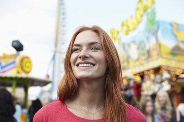 Smiling young woman on a funfair - RHF000362