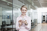 Germany, Munich, Businesswoman in office, using smart phone - RBYF000512