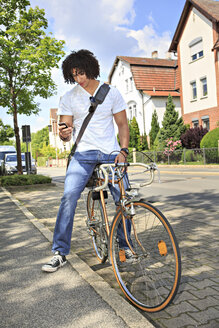 Young male student sitting on a bicycle looking at his smartphone - VTF000283
