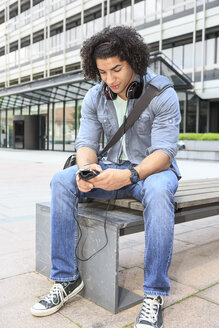 Young male student sitting on bench using his smartphone - VTF000289