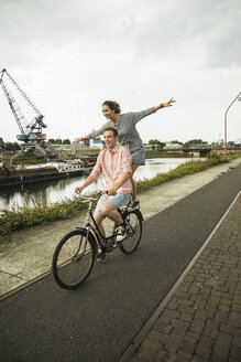 Young couple driving together on bicycle - UUF001043