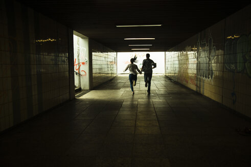 Young couple running hand in hand in a dark underpass, partial view - UUF001075