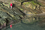 New Zealand, Golden Bay, Puponga, boy in a cave with pool of water - SHF001487