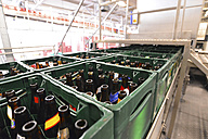 Germany, beer crates with empty bottles on an assembly line of a brewery - SCH000296