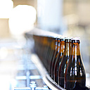 Germany, beer bottles on an assembly line of a bottling plant of a brewery - SCH000288