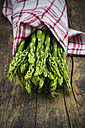 Bunch of green asparagus, Asparagus officinalis, wrapped in kitchen towel lying on dark wood - LV001445