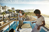 Friends playing urban golf on highboard of a swimming pool - VV000122
