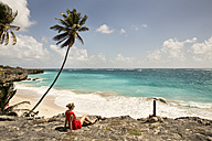 Caribbean, Barbados, Bottom Bay, woman sitting at the coast - SKF001543