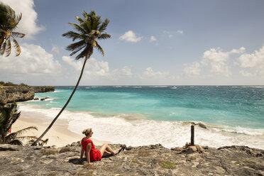 Caribbean, Barbados, Bottom Bay, woman sitting at the coast - SKF001543