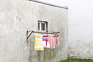 Germany, glum backyard with children's dresses hanging on clothes pole - DR000693