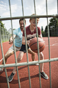 Germany, Mannheim, Father and son playing basket ball - UUF001170