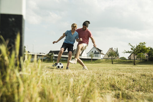 Germany, Mannheim, Father and son playing soccer - UUF001118