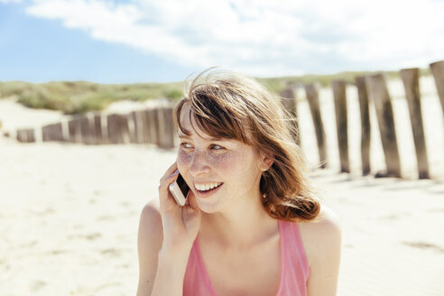 Portrait of woman telephoning with her smartphone on the beach - MFF001133