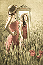 Teenage girl with summer dress and hat standing in wheat field looking at her image in mirror - FCF000264