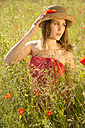 Portrait of teenage girl with summer hat on meadow with poppies - FCF000266