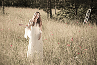 Portrait of teenage girl wearing white dress standing on meadow at backlight - FCF000269