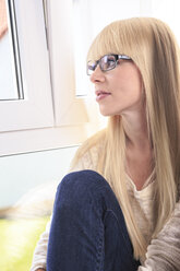 Portrait of a young woman wearing glasses looking out of window - VTF000302