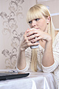 Portrait of a young woman with a cup using laptop at home - VTF000304