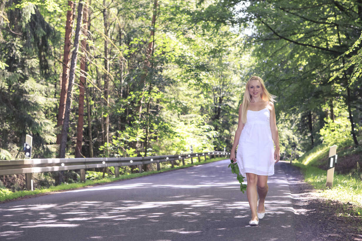 Portrait of a young woman wearing white dress walking on country road - VTF000309 - Val Thoermer/Westend61