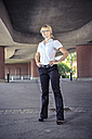 Young woman wearing business clothes standing at underpass - VT000314