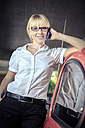 Portrait of smiling young woman telephoning with smartphone leaning on car - VT000316