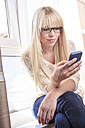Portrait of a young woman using smartphone at home - VTF000323