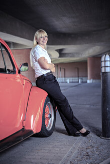 Portrait of a smiling young woman sitting on car wing of a classic car - VTF000327