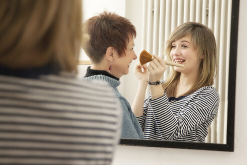 Germany, Berlin, Mother and daughter applying make up - MMFF000017