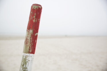Germany, Lower Saxony, East Friesland, Langeoog, red and white wooden stake in front of the beach - JATF000744