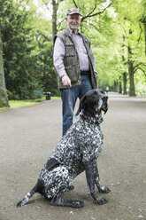 Senior man with his German Shorthaired Pointer in city park - JATF000734
