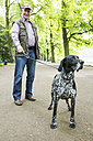 Senior man walking with his German Shorthaired Pointer in city park - JATF000752