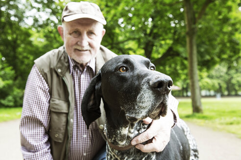 Portrait of senior man with his German Shorthaired Pointer in city park - JATF000736