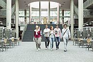 Group of students walking in a university library - WESTF019682