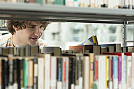 Student in a university library taking book from shelf - WESTF019723
