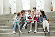 Group of students with books sitting on stairs - WESTF019760