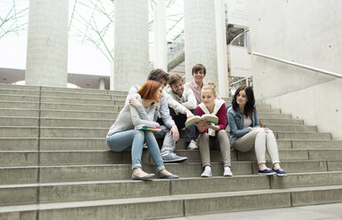 Group of students with books sitting on stairs - WESTF019761
