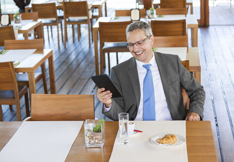 Businessman in restaurant with digital tablet - DISF000847