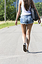 Portrait of young woman wwearing hot pants walking on road - DRF000701