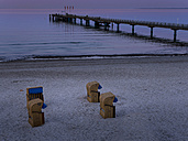 Germany, Schleswig-Holstein, Scharbeutz, Sea bridge and roofed wicker beach chairs at beach - AMF002462