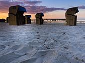 Germany, Schleswig-Holstein, Scharbeutz, Sea bridge, Roofed wicker beach chairs at beach in the evening - AMF002469