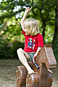 Little girl sitting on wooden horse at playground - JFE000413