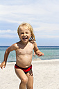 Portrait of smiling little girl running on beach - JFEF000427