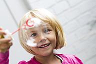 Portrait of little girl making soap bubble - JFEF000434