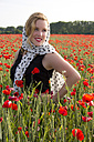 Portrait of smiling woman dressed in twenties style standing in poppy field - YFF000191