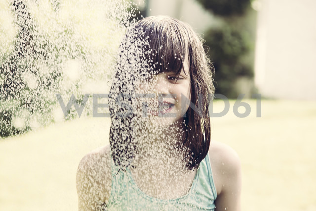 Portrait of little girl taking a shower in the garden - LVF001502