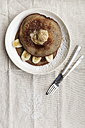 Plate of buckwheat pancake with banana slices and peanut butter on cloth, elevated view - EVG000648