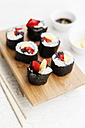 Futo Maki with mango and bell pepper on wooden board, dipping bowls and chop sticks - EVG000654